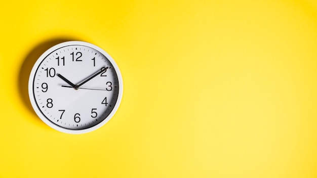 Круглые белые часы на желтом фоне стены