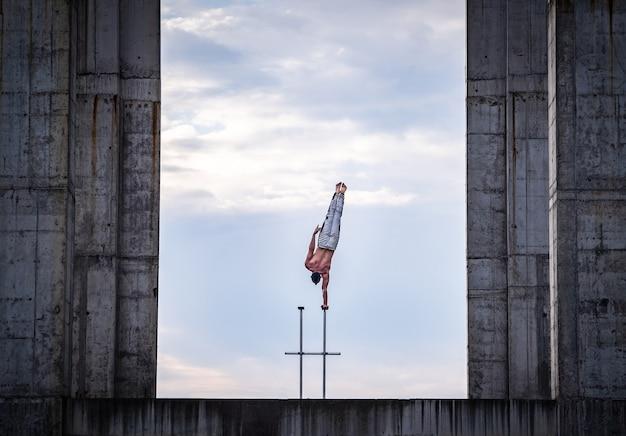 서커스 아티스트는 하늘과 산업 건설 배경에 한 손으로 균형을 유지합니다.