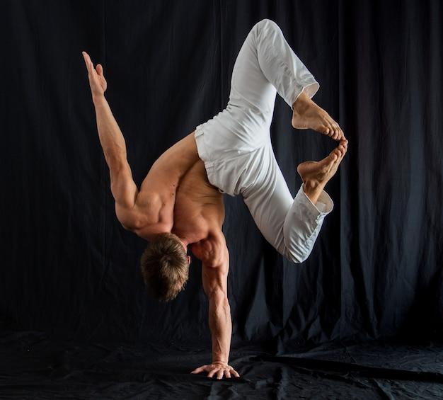 Артист цирка держит равновесие на одной руке