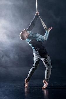 검정색과 훈제 배경에 의상을 입은 공중 스트랩에 서커스 예술가.