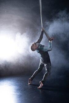 黒とスモークの衣装で空中ストラップのサーカスアーティスト。