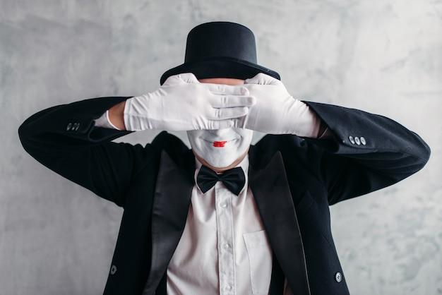 Артист цирка позирует, пантомима с белой маской макияжа. комедийный актер в костюме, перчатках и шляпе