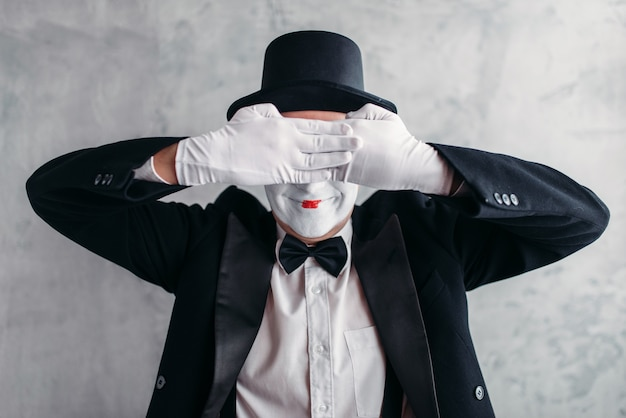 Circus artist posing, pantomime with white makeup mask. comedy actor in suit, gloves and hat