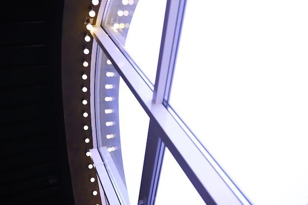 赤い天井に一列に並んだサーカスライト。建物の天井からぶら下がっているランプ。長蛇の列に並べる