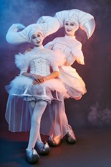 Артист цирка фокусник показывает трюки с мыльными пузырями. женщина и девушка надувают мыльные пузыри в цирке на шоу
