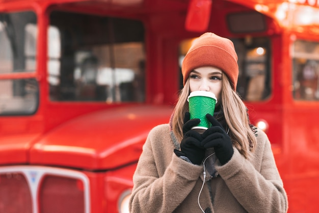 Cite lady in a warm coat and orange hat, standing in the street in the background of a red bus, drinking coffee from a paper cup, looking sideways