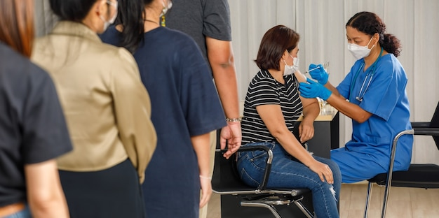 Citizens of different ages in a row standing and waiting for a vaccine injection while medical people injecting to senior woman in face mask. covid-19 or coronavirus vaccination concept.
