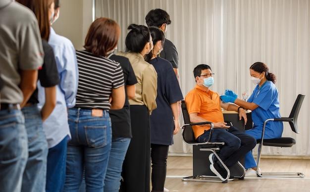 다양한 연령대의 시민들이 마스크를 쓴 노인에게 주사를 놓는 동안 백신 주사를 기다리고 있습니다. 코비드-19 또는 코로나바이러스 예방 접종 개념.
