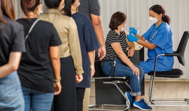 다양한 연령대의 시민들이 마스크를 쓴 노인 여성에게 주사를 놓는 동안 백신 주사를 기다리고 있습니다. 코비드-19 또는 코로나바이러스 예방 접종 개념.