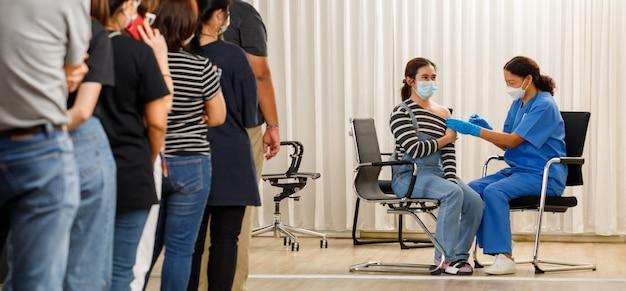 다양한 연령대의 시민들이 마스크를 쓴 젊은 여성에게 주사를 놓는 동안 백신 주사를 기다리고 있습니다. 코비드-19 또는 코로나바이러스 백신 서비스 개념.
