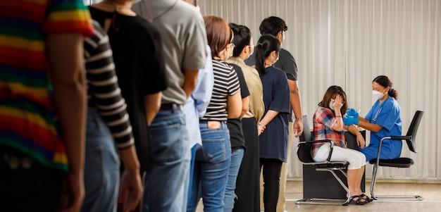 다양한 연령대의 시민들이 백신 주사를 기다리고 있고 의료인들은 얼굴 마스크에 여성을 주사합니다. 코비드-19 또는 코로나바이러스 예방 접종 개념
