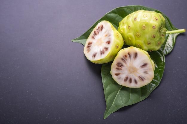 Плод великой моринды (нони) или моринда citrifolia дерево и зеленый лист на черном камне
