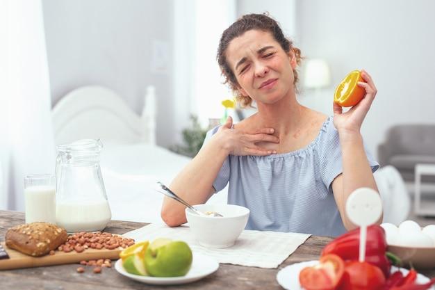 柑橘類アレルギー。夕食時にオレンジを食べている間、痛みとアレルギー性発疹を探している若い美しい女性