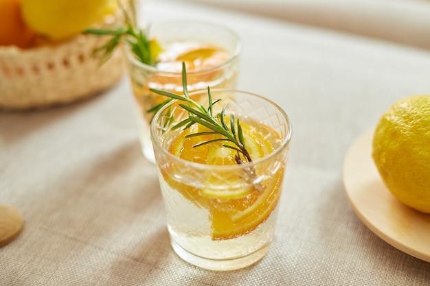 家の白いテーブルの上のガラスに柑橘類とローズマリーの新鮮なレモネード、夏の飲み物、デトックスの健康的な水。