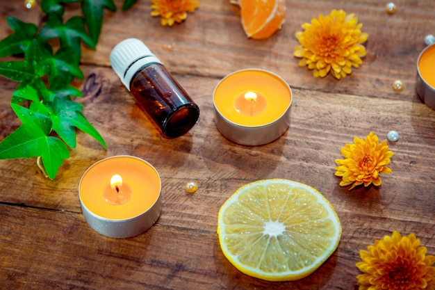 Citrus aroma oil concept. essential glass bottle, aroma candles, flowers, lemon slice on wooden background