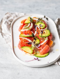 Citrus, avocado and fennel salad with dressing and purple sprouts