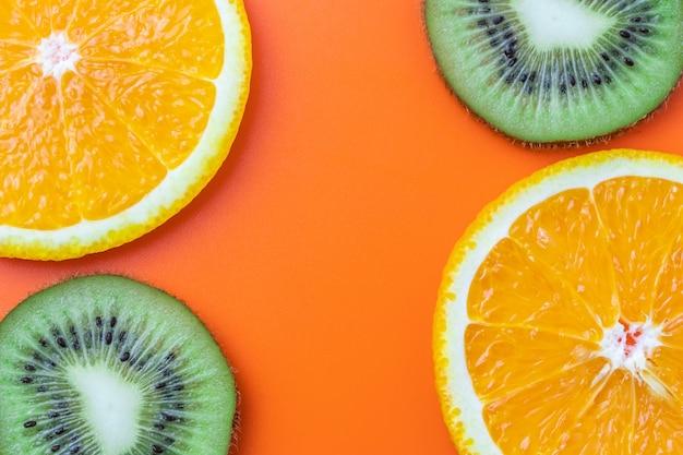 柑橘類の背景、スライスしたオレンジとキウイ。トロピカルフルーツのパターン、壁紙