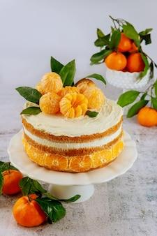 新鮮なタンジェリンと葉で飾られた柑橘系のケーキ。