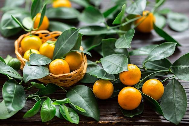 木の板のバスケットに葉を持つ柑橘類のカラマンシー