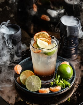 Citrus cocktail with orange and lime slices around smoked glasses