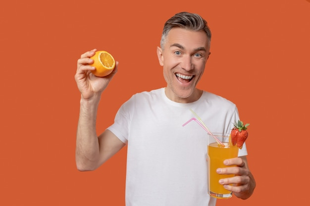 柑橘系の飲み物。絞りたてのジュースとオレンジのグラスを手に白いtシャツを着た熱狂的な笑顔の大人の男