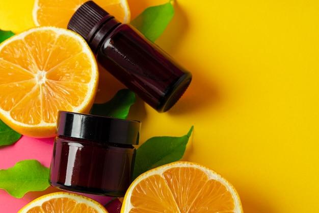 Citrus essential oil. sliced citrus fruit and aroma bottles on pink background