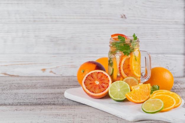 해독을위한 감귤류 과일 및 허브 물 또는 나무 보드에 유리 병에 다이어트