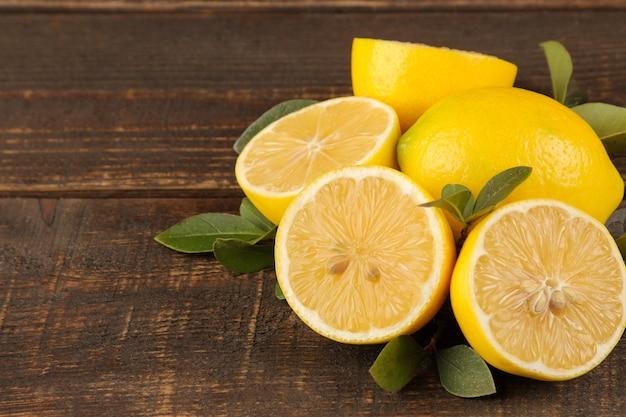 かんきつ類の果実。茶色の木製テーブルに葉とレモンスライスと新鮮なレモン。閉じる