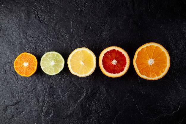 柑橘系の果物は、暗い石の背景に1列にレモンタンジェリンライムオレンジを半分にします