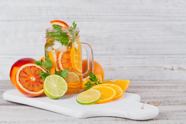 Citrus fruit and herbs water for detox or dieting in glass bottles on wooden board
