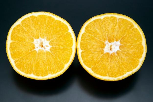 감귤류 과일은 어두운 배경에 오렌지 과일을 슬라이스