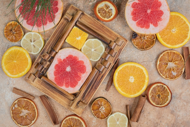 Citrus fruit slices in picture frame with bunch of fruits. high quality photo