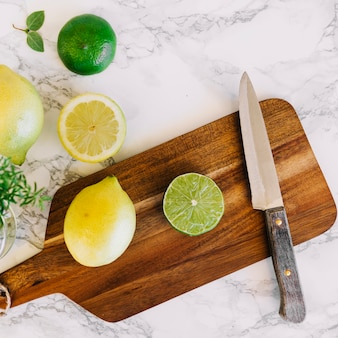 Citrus fruits and knife on wooden chopping board