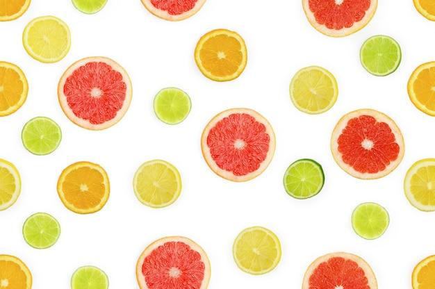 柑橘系の果物の背景。オレンジ、レモン、ライム、グレープフルーツの断片とのシームレスなパターン。