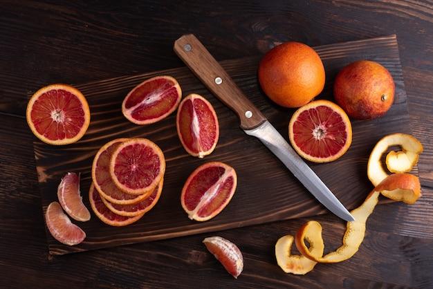 Цитрусовые, апельсины на разделочной доске с ножом Premium Фотографии