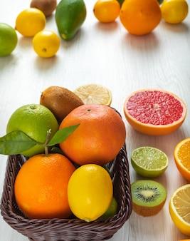 柑橘系の果物カラフルなアボカドレモンキウイオレンジテーブルの上のバスケットに