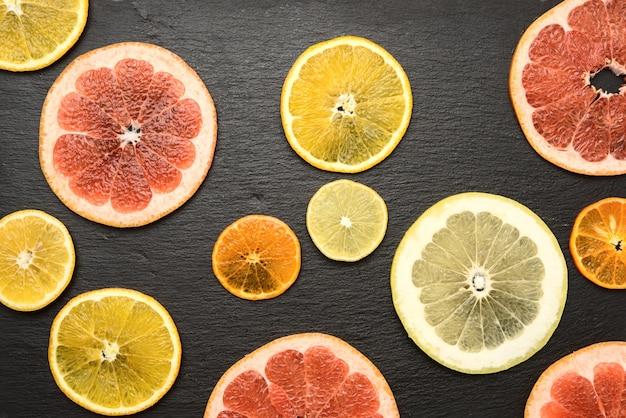 Цитрусовые нарезать круглыми кусочками: апельсин, грейпфрут, лимон, мандарин. спелые и сочные фрукты на черном фоне