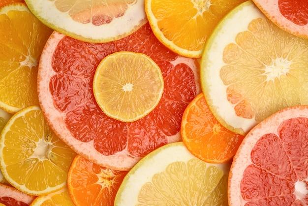 Цитрусовые нарезать круглыми кусочками: апельсин, грейпфрут, лимон, мандарин. спелые и сочные фрукты, вид сверху