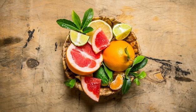 柑橘系の果物-グレープフルーツ、オレンジ、みかん、レモン、ライム、木製のテーブルに葉が付いたバスケット。上面図