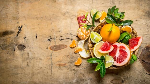 柑橘系の果物-グレープフルーツ、オレンジ、みかん、レモン、ライムの葉の入ったバスケット