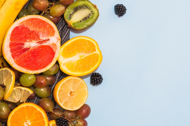 Citrus fruits; grapes and blackberries on blue backdrop