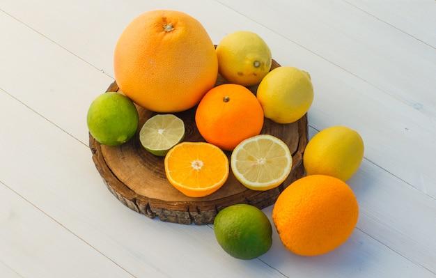 Цитрусовые фрукты под высоким углом обзора на разделочной доске и деревянном фоне