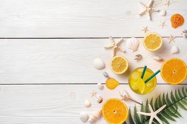 Цитрусовые, коктейль со льдом, ракушки и морские звезды на белом деревянном фоне.