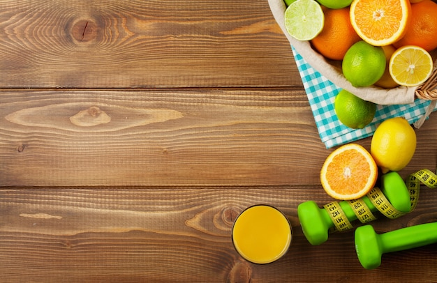 バスケットとダンベルの柑橘系の果物。オレンジ、ライム、レモン。コピースペースと木製のテーブルの背景の上
