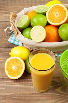 바구니에 든 감귤류와 주스 한 잔. 오렌지, 라임, 레몬. 흰색 나무 테이블 배경 위에