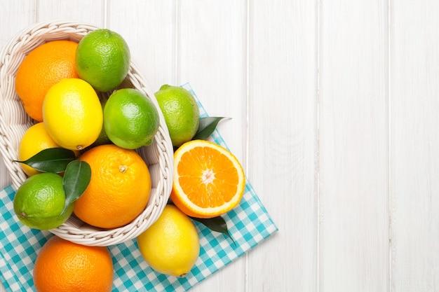 바구니에 감귤류 과일입니다. 오렌지, 라임, 레몬. 복사 공간이 있는 흰색 나무 테이블 배경 위에