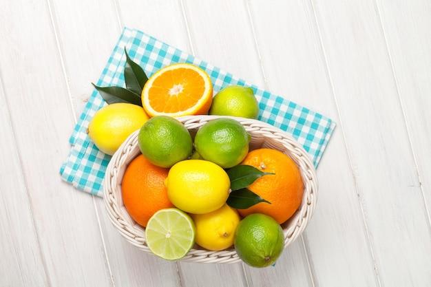 바구니에 감귤류 과일입니다. 오렌지, 라임, 레몬. 흰색 나무 테이블 배경 위에