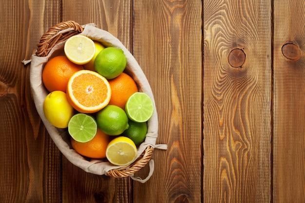 바구니에 감귤류 과일입니다. 오렌지, 라임, 레몬. 복사 공간이 있는 나무 테이블 배경 위에
