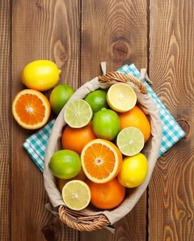 바구니에 감귤류 과일입니다. 오렌지, 라임, 레몬. 나무 테이블 배경 위에