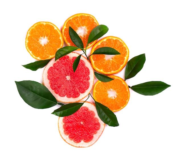 Цитрусовые фрукты, изолированные на белом. изолированные цитрусовые. части мандарина, розового грейпфрута и апельсина изолированные на белизне, с путем клиппирования. вид сверху.
